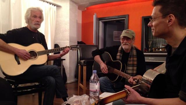 Drei Gitarristen sitzen mit ihren Instrumenten an einem Tisch.
