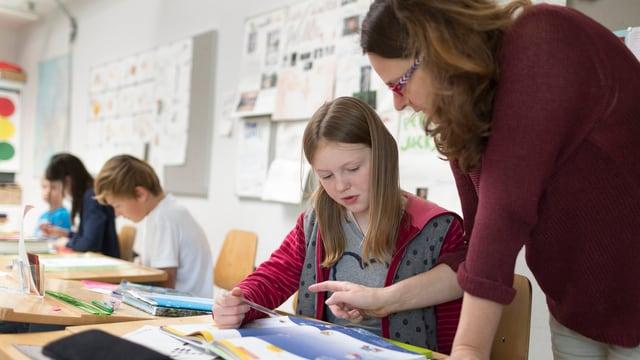 Eine Lehrerin steht neben dem Pult einer Schülerin und erklärt ihr eine Aufgabe.