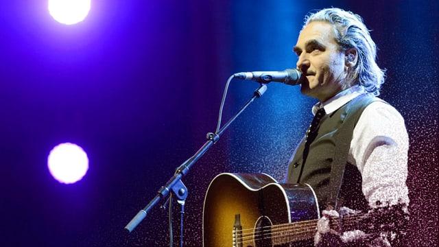Stephan Eicher mit Gitarre vor einem Mikrofon.