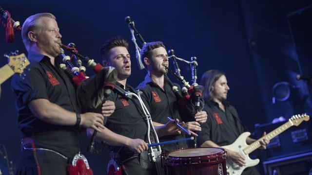 Die Red Hot Chilli Pipers spielen auf einer Bühne Dudelsack, E-Gitarre und die Trommel.