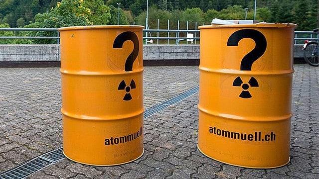 Zwei gelbe Atommüll-Fässer. Darauf sind zwei schwarze, grosse Fragezeichen gemalt.