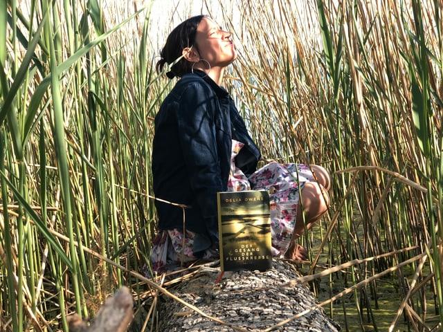 Annette König sitzt im Schilf. Vor ihr auf einem Baumstamm steht der Roman «Der Geang der Flusskrebse» von Delia Owens