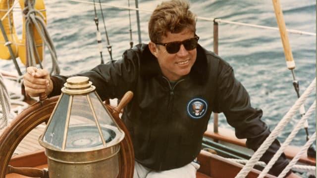 JFK sitzt an Bord der US Coast Guard Yacht Manitou bei der Küste von Maine.