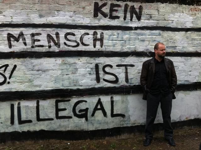 Ville Tietäväinen im Porträt. Hinten eine Mauer mit der Aufschrift «Kein Mensch ist illegal».