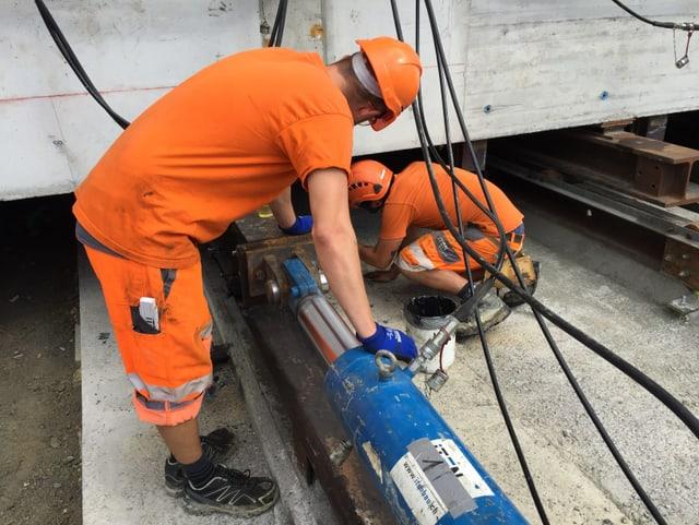 Zwei Arbeiter beugen sich über die Hydraulikpresse.
