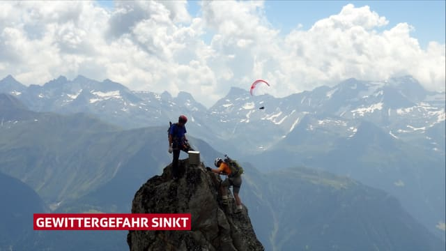 Zwei Kletterer auf einem Gipfel, dahinter Bergkulisse mit Quellwolken und Gleitschirmflieger.