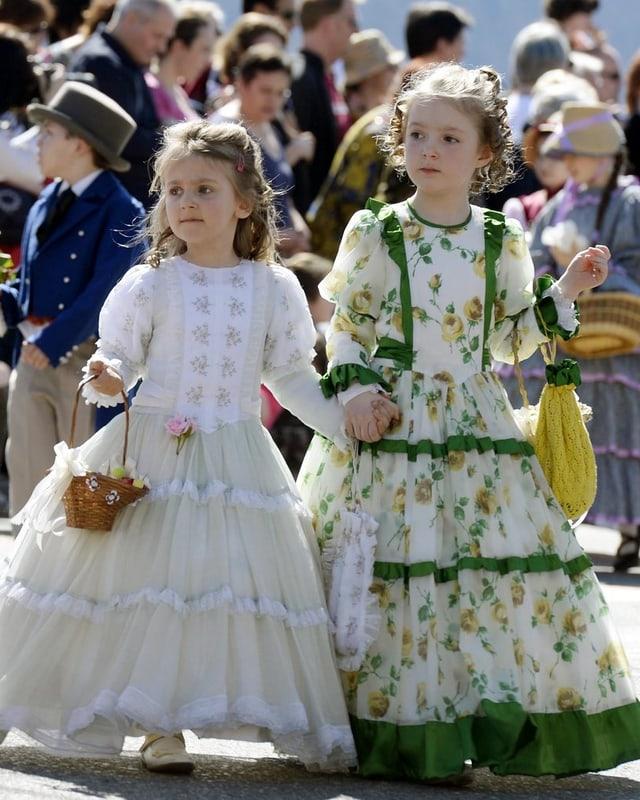 Zwei Mädchen in weissem und grün geblümten langen Kleidern.