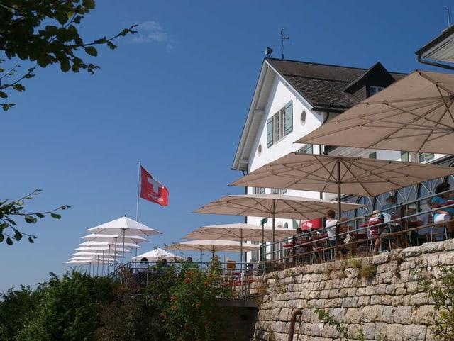 Hotel Weissenstein bei Sonnenschein. Sonnenterasse mit Sonnenschirmen. Im Hintergrund eine Schweizerflagge.