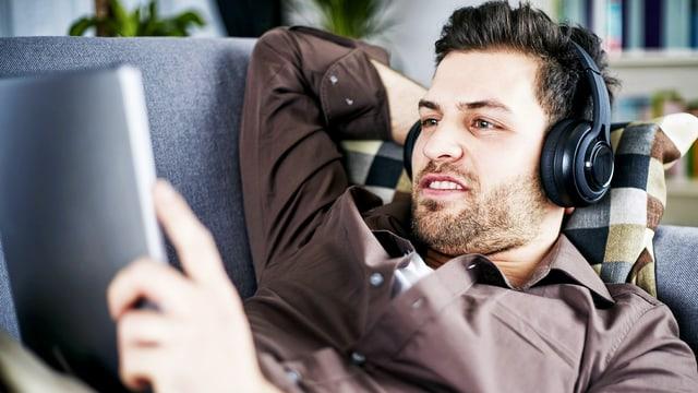 Ein junger Mann mit Dreitagebart liegt auf einem Sofa, trägt Kopfhörer und schaut in sein iPad.
