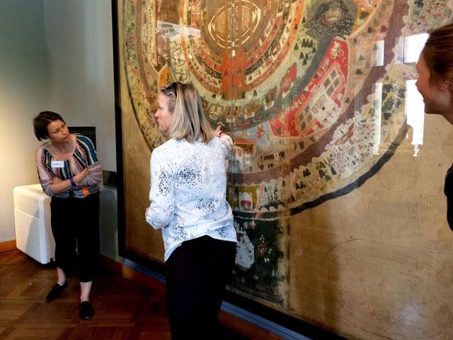 Drei Besucherinnen zeigen auf einen Punkt auf einem grossen, bunten Bild.