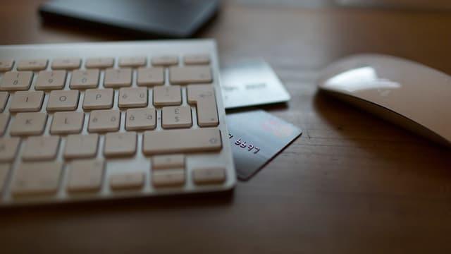 Eine Tastatur und eine Maus, weiss, und halb unter der Tastatur versteckt liegen zwei Bannkarten.
