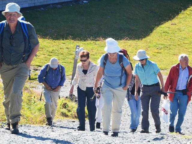 Eine Gruppe von Menschen steigt einen steilen Hang hinauf.