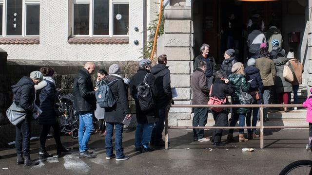 Leute stehen Schlage vor dem Eingang in ein Schulhaus um ihre Stimme abzugeben
