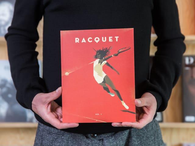 Jemand hält eine Zeitschrift in den Händen. Auf dem Cover die illustration eines Tennisspielers.