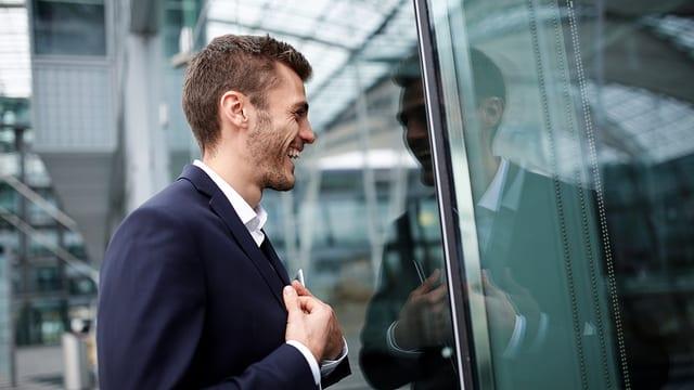 Ein Mann lacht sein Spiegelbild in einer Fensterscheibe an.