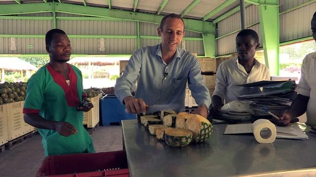 Maik Blaser schneidet Ananas, neben ihm zwei Angestellte