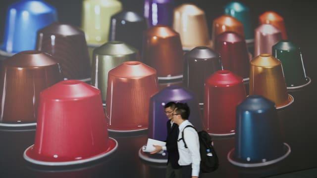 Zwei Asiaten stehen vor einem Plakat. Es zeigt riesige Nespresso-Kapseln.
