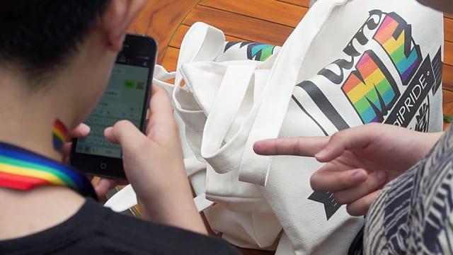 Ein Mann zeigt auf das Smartphone, das ein anderer in der Hand hält.