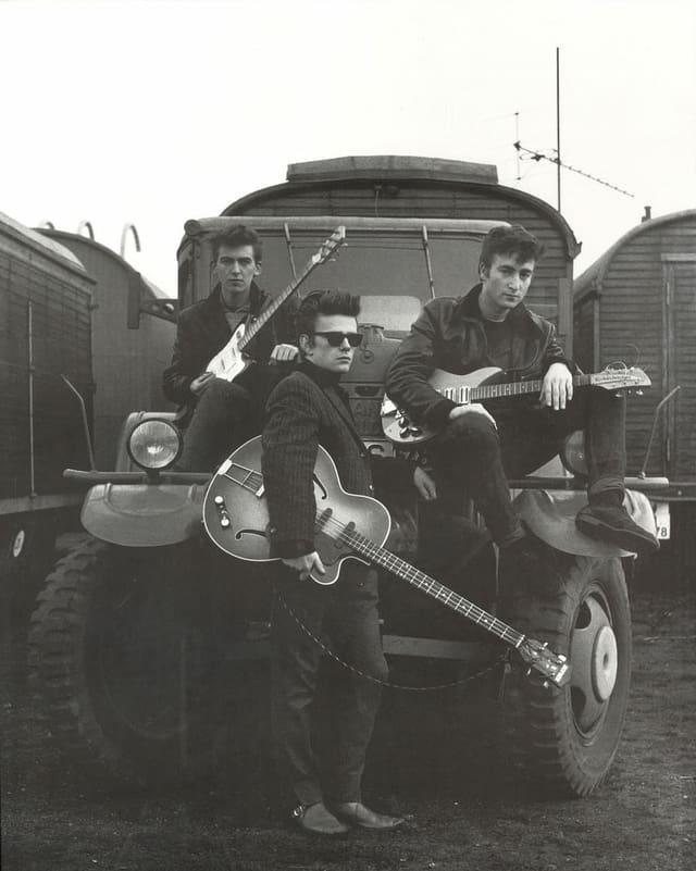 Drei junge Männer in Lederjacken posieren mit Gitarren.