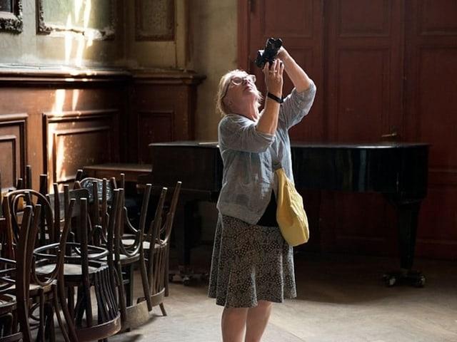 Eine Frau mit einer Kamera in der Hand steht in einem Raum mit Stühlen an den Wänden.