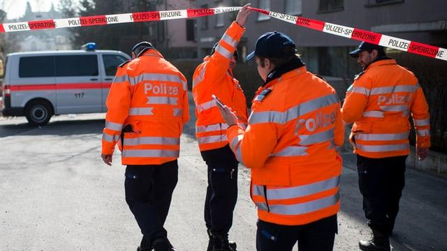 Vier Polizisten in Uniform, im Hintergrund ein Polizeiauto.