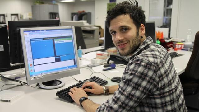 Sebalter sitzt an einem Computer, die Hände auf der Tastatur und lächelt.