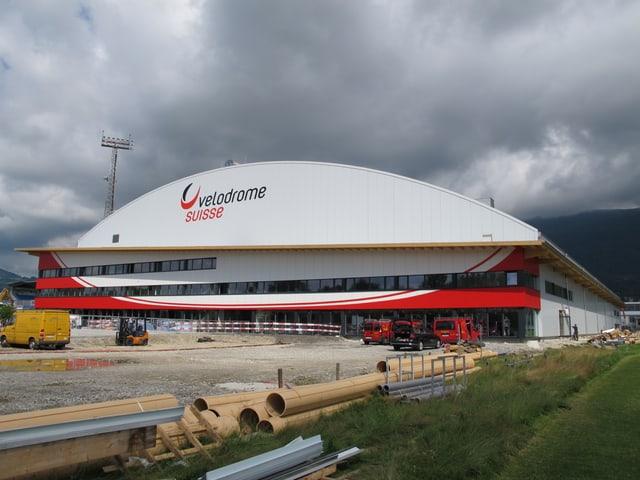 """Das Velodrome Grenchen hat ein leicht gewölbtes, weisses Dach, auf dem mittelgross """"velodrome suisse"""" mit schwarz-roter Farbe geschrieben steht. Ansonsten ist das Gebäude weiss, mit etwas rot. Im Vordergrund sieht man noch einige Rohre als Anzeichen dafür, dass die Bauarbeiten noch nicht ganz abgeschlossen sind."""