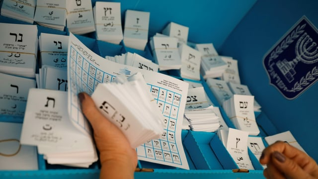 Eine Person sortiert aufgestapelte Wahlzettel.