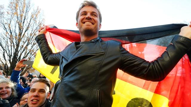 Nico Rosberg posiert mit der deutschen Flagge um die Schultern.