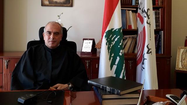 Pater Abdo Abou Kassm, ein älterer Mann, sitz an seinem Schreibtisch, hinter ihm ist die Flagge des Libanons.