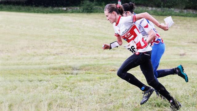 Die Orientierungsläuferin Judith Wyder sprintet auf einer Wiese gegen eine Konkurrentin.
