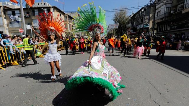 Zwei Frauen in bunten Kostümen laufen die Strasse herunter.