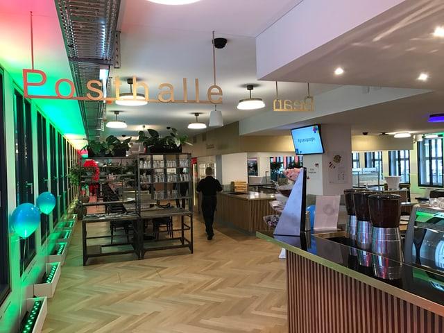 Das Restaurant mit Kaffeemaschinen und langen Tischen, Parkettböden und farbigem Licht.