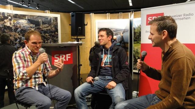 Drei Männer sitzen auf einer Bühne und sprechen mit Mikrofonen in der Hand miteinander.