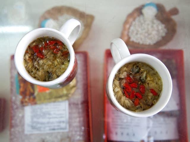 Tassen mit Kräutertee auf Teepackungen.