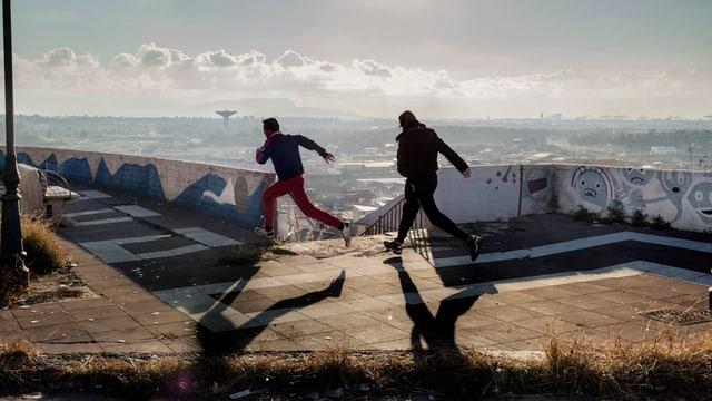 Zwei Jungen rennen im Zwielicht über eine Terrasse.