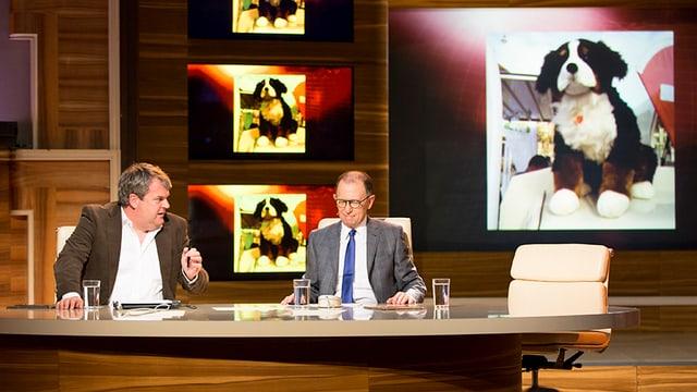Mike Müller und Viktor Giacobbo sitzen am Tisch und kommentieren ein Bild des neuen SVP-Maskottchens.