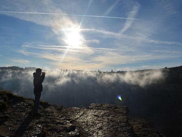 Ein Mann blickt im Gegenlicht auf den von Nebel erfüllten Creux du Van.