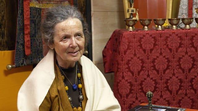 Anne Deriaz sitzt in ihrer buddhistischen Umgebung.