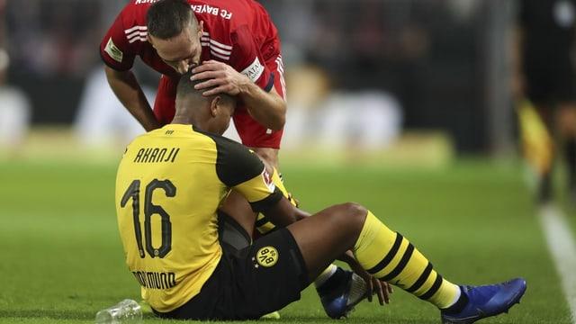 Manuel Akanji sitzend auf Rasen, bekommt küsschen von Franck Ribéry