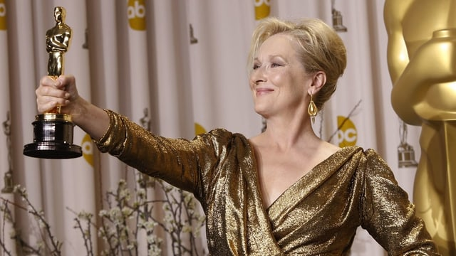 Meryl Streep lächelt und hält mit der rechten Hand den Oscar hoch.