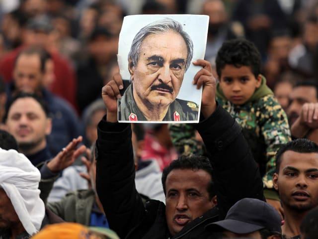 Mann hält Transparent mit Bild von Militärkommandant Kahlifa Haftar in die Luft, Benghazi, 17.12.17