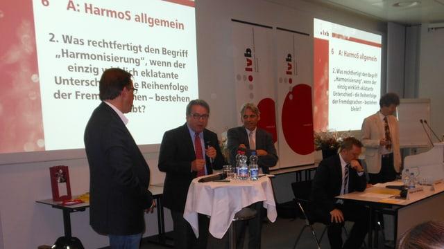 Bildungsdirektor Urs Wühtrich stehend an einem Rednerpult. Daneben weitere Mitarbeiter aus der Bildungsdirekton.