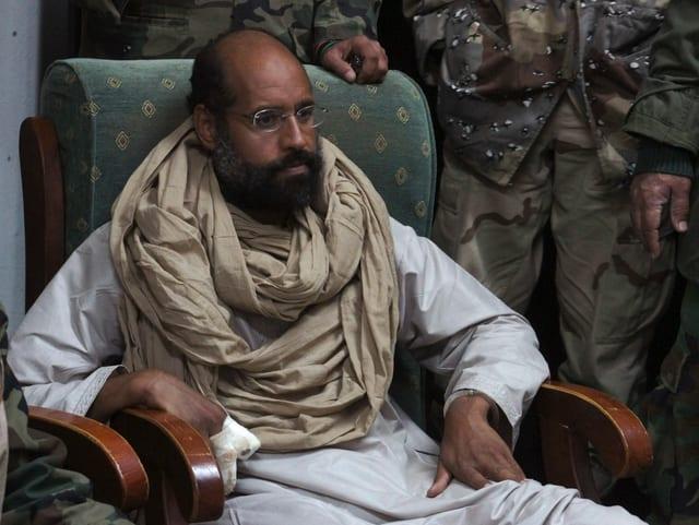 Saif al-Islam Gaddafi mit Bart umringt von Kämpfern.
