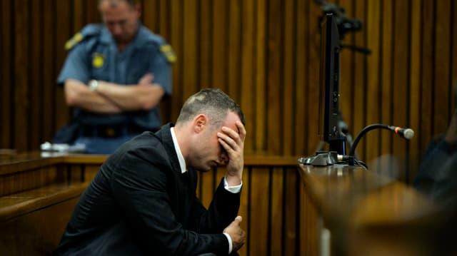 Oscar Pistorius sitzt alleine auf einer Bank im Gerichtssaal und stützt den Kopf mit seinen Händen