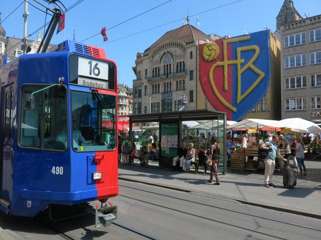 Ein Tram in FCB-Farben, im Hintergrund die Fassade des Globus mit rieser FCB-Flagge.