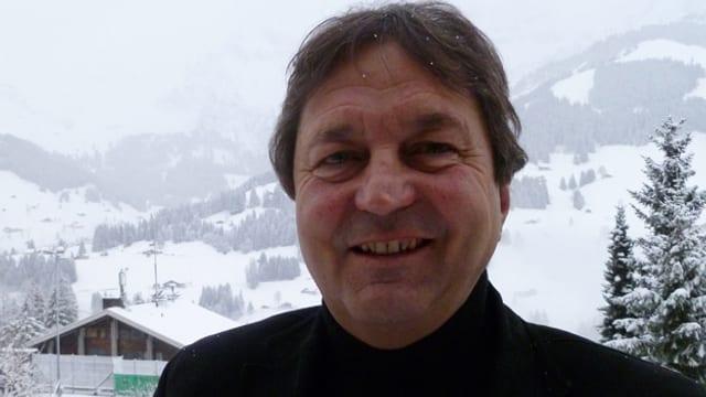 Jürg Blum steht vor den verschneiten Pisten von Adelboden.