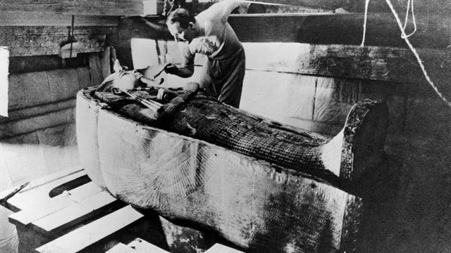 Howard Carter steht vor dem Sarg von Tutanchamun.