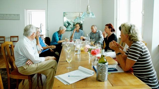 Eine Gruppe von Menschen sitzt am Tisch.