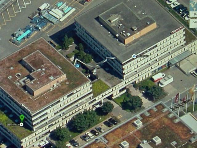 Vogelperspektive eines Gebäudes mit Parkplatz.